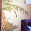photo of child's mural with large turtle under a palm plant.
